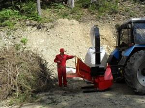 Рабочий уничтожает ветки при помощи дробилки