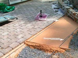 Установка направляющих в процессе укладки тротуарной плитки.