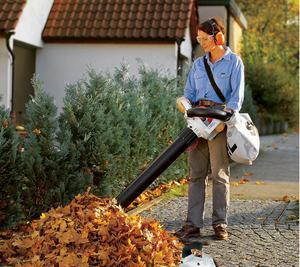 Женщина убирает листья при помощи садового пылесоса